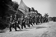 Peoples Liberation Army march into the town of Beichuan from their make shift base camp some 2km away. Their flag has the name of their regiment on the traditional communist red background