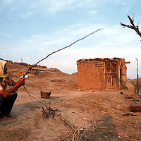 a sheperd from the Hui minority breaks firewood outside a shack on barren grasslands in central China's Ningxia province. According to the UNDP, desertfication has devoured 55.8%, or 2.89 million hectares of Ningxia's total terrain. An additional 1.21 million hectares grassland and 132.000 hectares farmland are under the threat of dsertification. The livelihood of inhabitants in 13 cities , 40 townships and 600 villages has been severely affected and the region's vulnerable natural environment is also at stake. Ningxia is one of the major sources of sandstorms which have a major impact on Northern China.<br /> Photo by @hessekatharina #desertification #climatechange #china #ningxia #globalwarming #climatechangeisreal