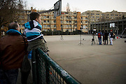 A child sits on the fence watching a production of a video clip in Bienne, Switzerland. Image © Angelos Giotopoulos/Falcon Photo Agency