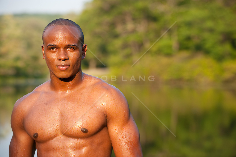 african american man without a shirt standing by a lake