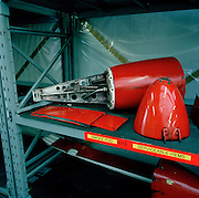 Stored temporarily in a storeroom shelf, are the front and rear sections of a Hawk jet aircraft smoke pod belonging to the elite 'Red Arrows', Britain's prestigious Royal Air Force aerobatic team. Grubby and old, like museum artifacts, the two items are attached to the ageing aircrafts' belly accessory that provides the team with their distinctive red, white and blue smoke (a vegetable dye and diesel fuel mixture) during their air show display routines. This version of the BAE Systems Hawks are primitive pieces of equipment, without computers or fly-by-wire technology. Nevertheless, the team's aircraft are in some cases over 20 years old and their air-frames require constant attention with increasingly frequent major overhauls due. Here the parts are separated from the middle section which are receiving a winter modification.