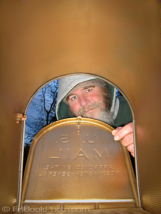a mature bearded man looks favorably into a gold mailbox as viewed from inside