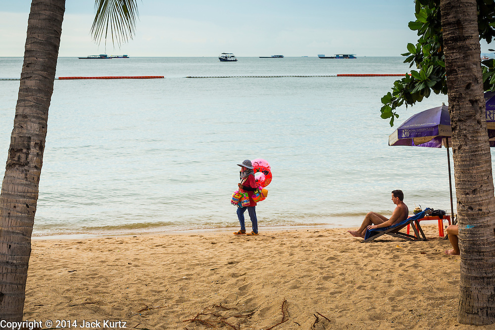"""26 SEPTEMBER 2014 - PATTAYA, CHONBURI, THAILAND: A vendor who sells inflatable toys walks past a tourist on Pataya Beach. Pataya, a beach resort about two hours from Bangkok, has wrestled with a reputation of having a high crime rate and being a haven for sex tourism. After the coup in May, the military government cracked down on other Thai beach resorts, notably Phuket and Hua Hin, putting military officers in charge of law enforcement and cleaning up unlicensed businesses that encroached on beaches. Pattaya city officials have launched their own crackdown and clean up in order to prevent a military crackdown. City officials have vowed to remake Pattaya as a """"family friendly"""" destination. City police and tourist police now patrol """"Walking Street,"""" Pattaya's notorious red light district, and officials are cracking down on unlicensed businesses on the beach.     PHOTO BY JACK KURTZ"""