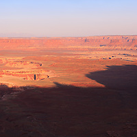 Morning sun illuminates a wide canyon in the Island In the Sky district of Canyonlands National Park, Utah.