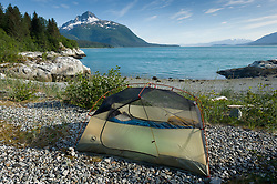 Kayakers picked a beach near the Klotz Hills to set up their tent. The location is not far from Maquinna Cove in Muir Inlet in Glacier Bay National Park and Preserve in southeast Alaska. Prominent in the background is Mt. Wright which is located at the mouth of Adams Inlet.