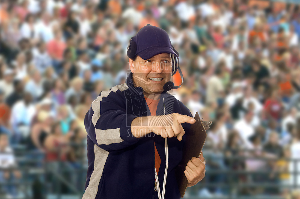 Coach wearing a headset on the field against a crowd