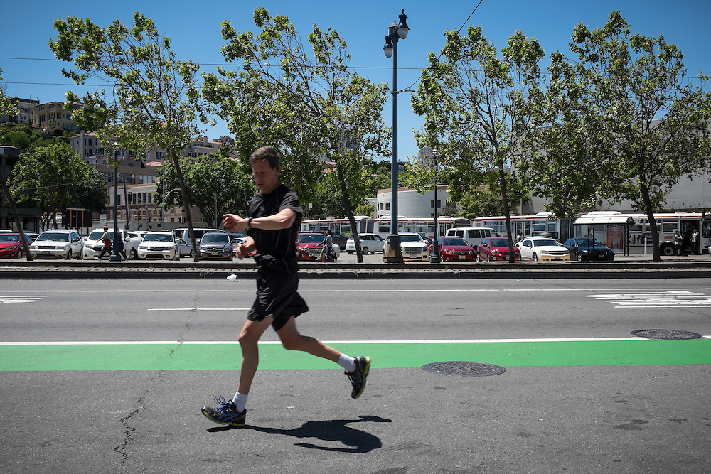 Runner in street avoiding the crowds on the Embarcadero's Promenade | May 6, 2014
