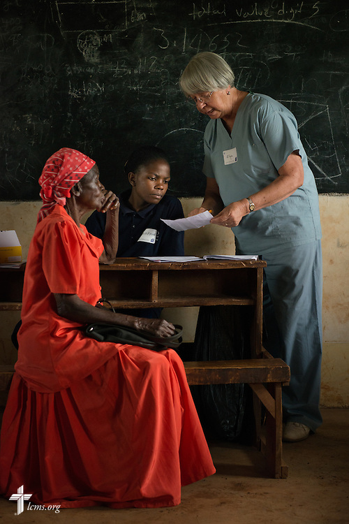 Elga Heintzen, a nurse from Hinsdale, Ill., attending First St. Paul Lutheran Church, works with a Kenyan health worker as the two treat an elderly woman at the Mercy Medical Team clinic Wednesday, June 11, 2014, at the Luanda Doho Primary School in Kakmega County, Kenya. LCMS Communications/Erik M. Lunsford