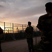 Army officers stand guard at the 12.5-kilometer barbed-wire fence along the land border with Turkey, which was met with skepticism at home as well as from many EU officials.  It has allegedly succeeded in blocking one of the most popular transit routes for migrants seeking to make their way to the West.   Image © Angelos Giotopoulos/Falcon Photo Agency