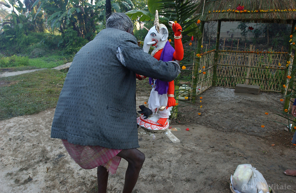 "Villagers, many of whom lost their homes, crops, and even a man who was killed by elephants perform a ""puja"" or holy ceremony to the Hindu God Lord Ganesha who is half human and half elephant to ask him to protect the village from real elephants coming back and causing more destruction  near Tezpur in Assam, eastern India January 6, 2004.  Villagers have been forced to stay up lighting fires, banging tin cans, throwing firecrackers to keep elephants from destroying their crops, homes and somtimes killing people. India and its sacred elephants are threatened by the deforestation caused by encroachment of the reserved land and natural forests.  As a result, wild elephants are rampaging through villages, killing people and destroying their homes and crops. (Ami Vitale)"