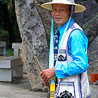 Asia, China, Kunming. Ethnic minority male, part of a group dancing at the Stone Forest.