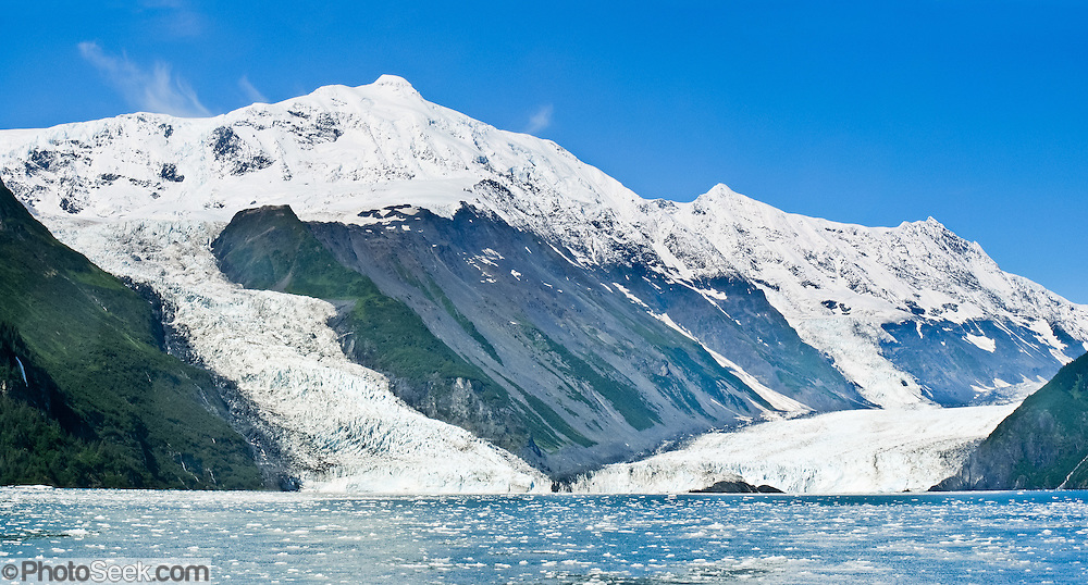The tidewater Cascade and Barry Glaciers pour from the steep and glaciated Chugach Mountains into Barry Arm of Prince William Sound, Alaska, USA. Prince William Sound is surrounded by Chugach National Forest (the second largest national forest in the USA). Tour spectacular Prince William Sound by commercial boat from Whittier, which sits strategically on Kenai Peninsula at the head of Passage Canal. Whittier is a port for the Alaska Marine Highway System, a ferry service which operates along the south-central coast, eastern Aleutian Islands, and the Inside Passage of Alaska and British Columbia, Canada. Cruise ships stop at the port of Whittier for passenger connections to Anchorage (by road 60 miles) and to the interior of Alaska via highway and rail (the Denali Express). Known by locals as the Whittier tunnel or the Portage tunnel, the Anton Anderson Memorial Tunnel links Whittier via Portage Glacier Highway to the Seward Highway and Anchorage. At 13,300 feet long (4050 m), it is the longest combined rail and highway tunnel in North America. Whittier was severely damaged by tsunamis triggered by the 1964 Good Friday Earthquake, when thirteen people died from waves reaching 43 feet high (13 meters). Panorama stitched from 2 overlapping photos.