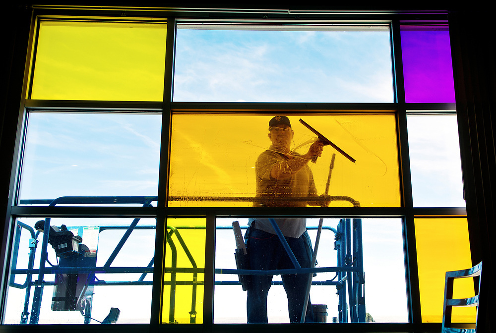 mkb033017/metro/Marla Brose --  John Miera, a window washer, cleans a wall of stained glass windows on the third floor of Isotopes Park, Thursday, March 30, 2017, in Albuquerque, N.M. Miera guessed that he was cleaning the inside and outside of about 2500 panes of glass at the park in preparation of opening night, next Thursday, when the Isotopes take on the Salt Lake Bees to kick off their 15th season in Albuquerque. (Marla Brose/Albuquerque Journal)