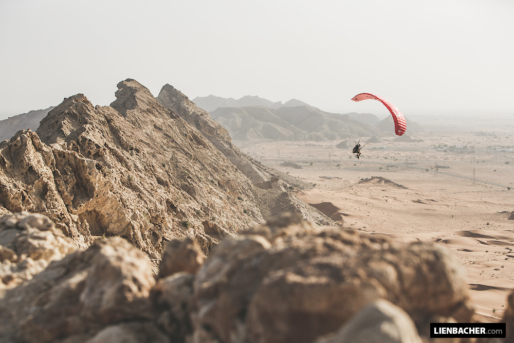 Dominic Roithmair soars his little cloud at a coral rock formation in the desert of Dubai. March 2015