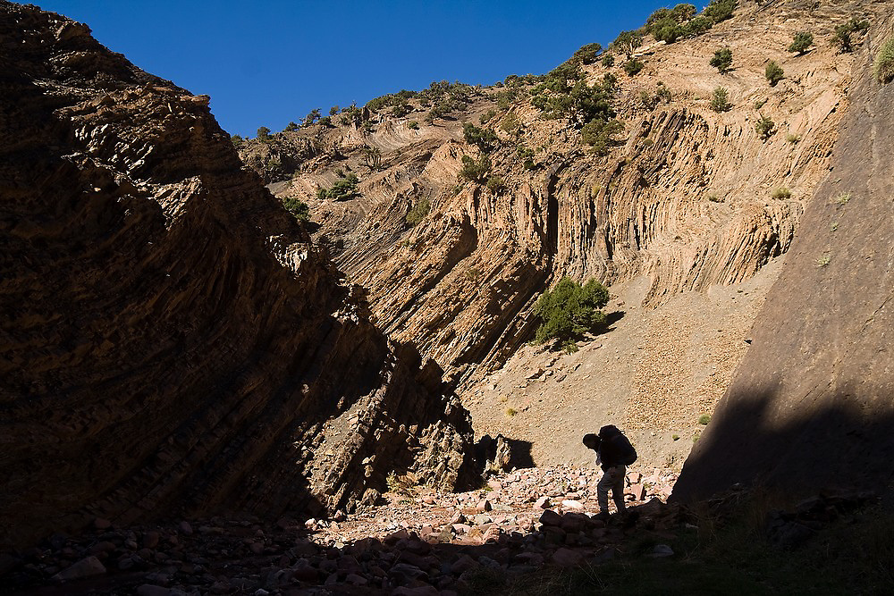 Liana Welty hikes through a narrow canyon towards Tizi n'Rougoult Pass from Rougoult in the M'Goun Massif, Central High Atlas Mountains, Morocco.
