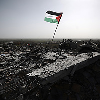 A Palestinian flag flutters in the rubble of a destroyed house following Israel's 22-days military offensive in the Hamas-run territory on January 25, 2009 in Jabalia, northern Gaza Strip. US peace envoy George Mitchell will find a region in disarray when he arrives this week on his first visit to try to cement a fragile ceasefire between Israel and Hamas militants.