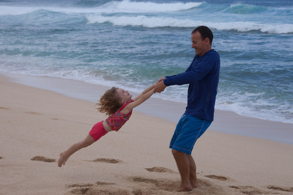 A father wswings his small daughter around on the beach on Oahu's north shore in Hawaii