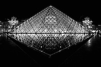 The Louvre Museum is one of the world's largest museums, the most visited museum in the world, and a historic monument. It is a central landmark of Paris, France and is located on the Right Bank of the Seine in the 1st arrondissement (district). Nearly 35,000 objects from prehistory to the 19th century are exhibited over an area of 60,600 square metres (652,300 square feet). The museum is housed in the Louvre Palace (Palais du Louvre) which began as a fortress built in the late 12th century. Remnants of the fortress are still visible. The building was extended many times to form the present Louvre Palace. The museum opened on 10 August 1793 with an exhibition of 537 paintings, the majority of the works being confiscated church and royal property. As of 2008, the collection is divided among eight curatorial departments: Egyptian Antiquities; Near Eastern Antiquities; Greek, Etruscan, and Roman Antiquities; Islamic Art; Sculpture; Decorative Arts; Paintings; Prints and Drawings.