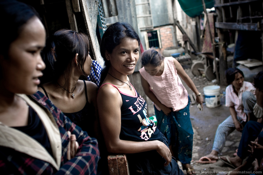 Prostitutes Srey Leat, left, Srey Dah, center, and Srey Bee, right,  relaxing before a night of sex work in a nearby park in Phnom Penh, Cambodia. She lives with other prostitutes in a downtown slum known for its gangs, pimps, prostitutes, and high rate of HIV.