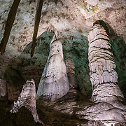 Large columns, in Carlsbad Caverns National Park, in the Guadalupe Mountains, Chihuahuan Desert, southeast New Mexico, USA. Hike in on your own via the natural entrance or take an elevator from the visitor center. Geology: 4 to 6 million years ago, an acid bath in the water table slowly dissolved the underground rooms of Carlsbad Caverns, which then drained along with the uplift of the Guadalupe Mountains. The Guadalupe Mountains are the uplifted part of the ancient Capitan Reef which thrived along the edge of an inland sea more than 250 million years ago during Permian time. Carlsbad Caverns National Park protects part of the Capitan Reef, one of the best-preserved, exposed Permian-age fossil reefs in the world. The park's magnificent speleothems (cave formations) are due to rain and snowmelt soaking through soil and limestone rock, dripping into a cave, evaporating and depositing dissolved minerals. Drip-by-drip, over the past million years or so, Carlsbad Cavern has slowly been decorating itself. The slowest drips tend to stay on the ceiling (as stalactites, soda straws, draperies, ribbons or curtains). The faster drips are more likely to decorate the floor (with stalagmites, totem poles, flowstone, rim stone dams, lily pads, shelves, and cave pools). Today, due to the dry desert climate, few speleothems inside any Guadalupe Mountains caves are wet enough to actively grow. Most speleothems inside Carlsbad Cavern would have been much more active during the last ice age-up to around 10,000 years ago, but are now mostly inactive.