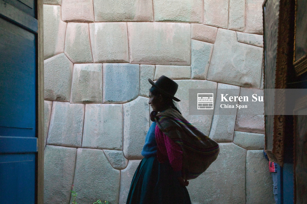 View of Indian woman by ancient Inca walls of polygonal stones through gateway, Cuzco, Peru