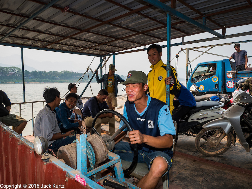 11 MARCH 2016 - LUANG PRABANG, LAOS:   A crewman steers a ferry across the Mekong River near Luang Prabang. Laos is one of the poorest countries in Southeast Asia. Tourism and hydroelectric dams along the rivers that run through the country are driving the legal economy.     PHOTO BY JACK KURTZ