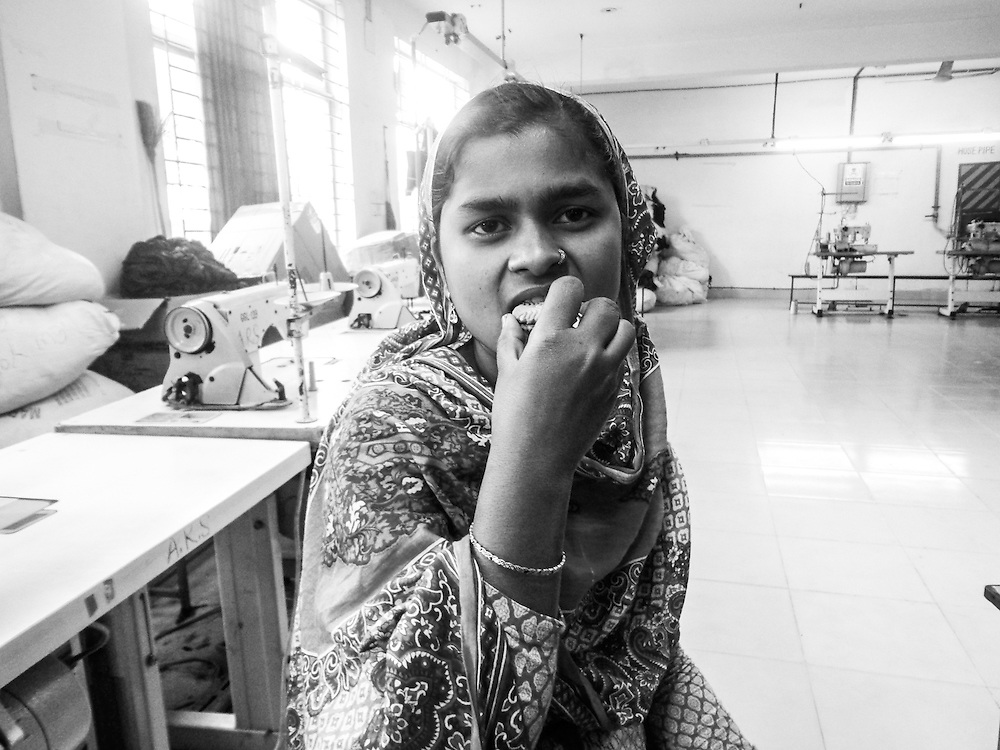- Taken by a female photographer on one of our photography programs in Bangladesh, depicting a female garment worker taking a cookie break.