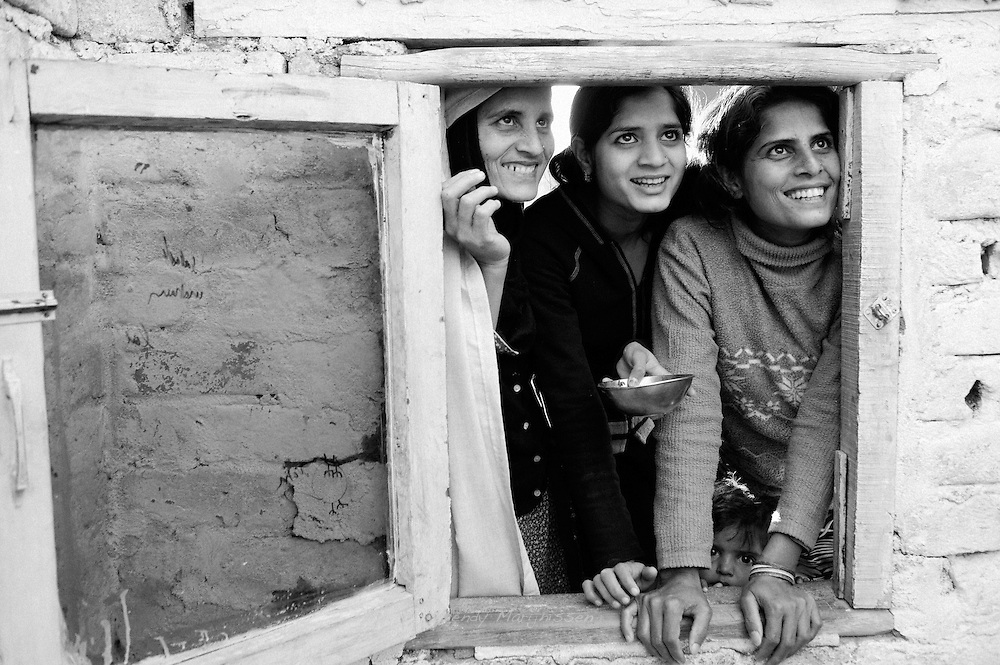 Women are laughing and joking though a window with their neighbours in the French colony slum.