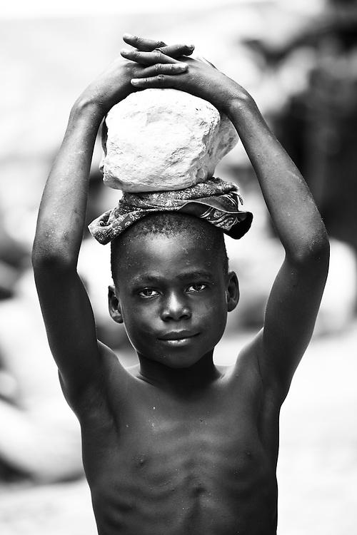 A boy carries a rock on his head in Marigot market, Haiti