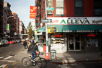 Woman riding a bike through Little Italy in Manhattan, New York City.