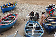 Fishermen play checkers between their boats after fishing in Taghazout, Morocco.