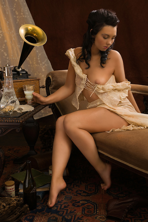 Scene set in Paris circa Paris 1910. A beautiful young woman listens to music while enjoying a glass of absinthe. Model - Sabrina Sin