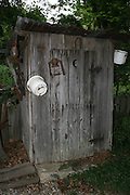 "A Country outhouse with antique pots and lamps hanging from it's sides, and with the classic ""crescent moon"" on the door."