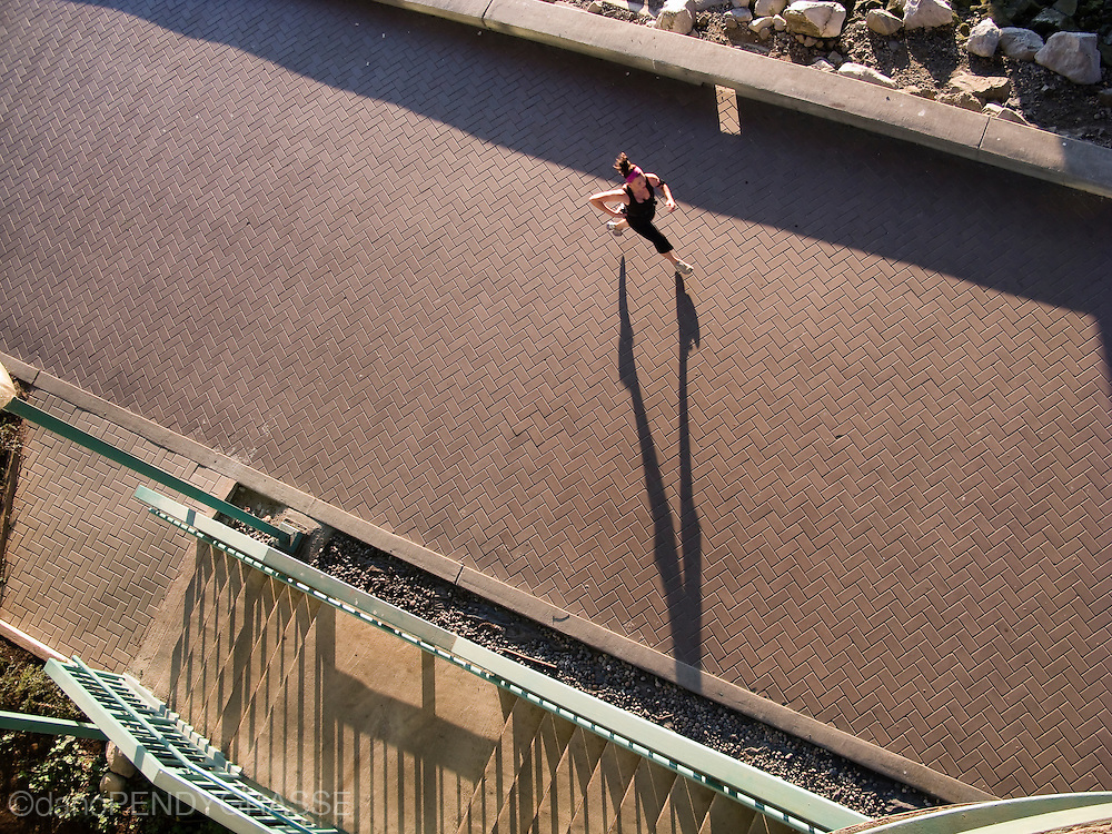 A woman is viewed from above, jogging in the late afternoon light, along Vancouver's False Creek seawall.