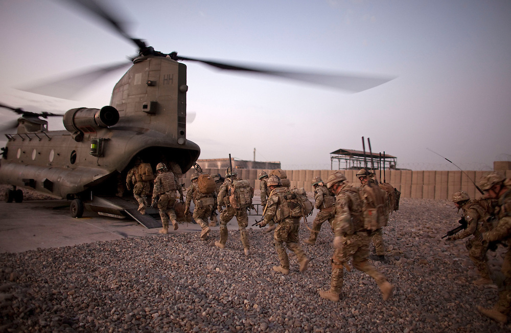 British soldiers from 1PWRR (Princess of Wales's Royal Regiment) board a CH-47 Chinook helicopter in preparation for an air assault into a contested region of Helmand Province. The men are involved in an ongoing series of Operations called Tora Pishaw aimed at disrupting insurgent activity in their AO (Area of Operations). During the most recent 4 day operation the soldiers regularly came under fire from insurgents using small arms, belt fed machine guns and UGL's (Under Slung Grenade Launchers). The soldiers returned fire using shallow trenches on the edges of ploughed fields or irrigation ditches as cover. Nad I Ali North, Helmand Province, Afghanistan on the 13th of November 2011.