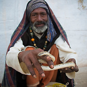 Snake charming is the practice of apparently hypnotising a snake by simply playing an instrument. A typical performance may also include handling the snakes or performing other seemingly dangerous acts, as well as other street performance staples, like juggling  and sleight of hand. The practice is very common in India. Many snake charmers live a wandering existence, visiting towns and villages on market  days and during festivals. The most popular species are those native to the snake charmer's home region, typically various kinds of cobras, though vipers and other types are also used. [source: Wikipadia]