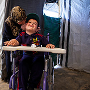 2015 April&mdash;Zaatari camp for Syrian refugees, Jordan. Against all odds, Khalid, 7, from Daraa, Syria, is the top student in his first grade class. This fortitudinous young man lost his mother at age three, he has been separated from his father for over two years by war, and he is physically disabled with muscular dystrophy. Khalid and his stepmother, Dilal, fled to Jordan for what they thought would be around a month stay&mdash;until the war quieted down. Due to the continued unrest in Syria they have lived in Zaatari camp for over two years.  <br /> <br /> Dilal whispering in Khalid's ear before the walk from their caravan to school.