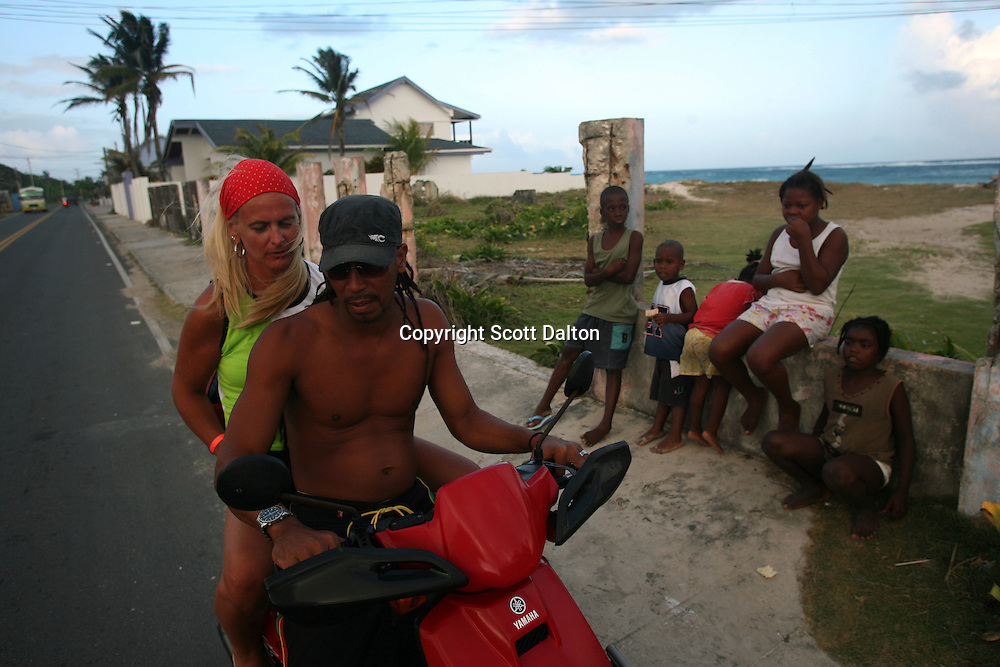 Constanza Jauregui, a tourist from Argentina, gets a lift on a motorbike in San Luis, a section of San Andres, a small island in the Caribbean, on Thursday, January 24, 2008. San Andres belongs to Colombia, although the territory and water rights have long been disputed with Nicaragua. But now there is a movement among the local population, who call themselves Raizal, mainly of African decent, calling for independence. (Photo/Scott Dalton).