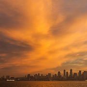 A golden sunrise colors the clouds above downtown Seattle, Washington as a ferry crosses Elliott Bay. The Space Needle, built for the 1962 Worlds Fair, is visible at the left edge of the image; the Columbia Center, Seattle's tallest skyscraper with a height of 933 feet (284 meters), is visible at the right.