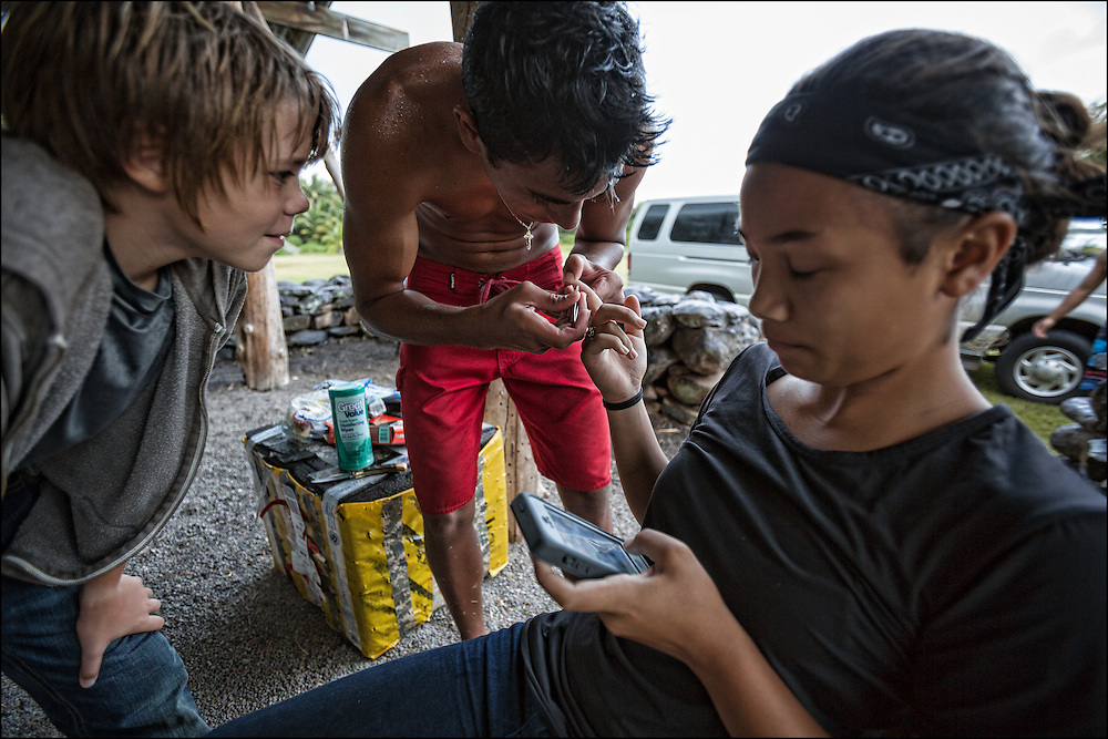 At the Ho'ea Initiative base camp located at the Keawanui Fishpond on Molokai, Karina Jacany calmly checks her phone for messages as Kai Kahoaliki Fonseca takes out a splinter in her finger while Alex Johnston looks on.