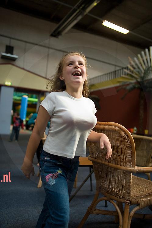 meisje heeft ballen uit de ballenbak onder haar t-shirt gestopt zodat het lijkt alsof zij borsten heeft