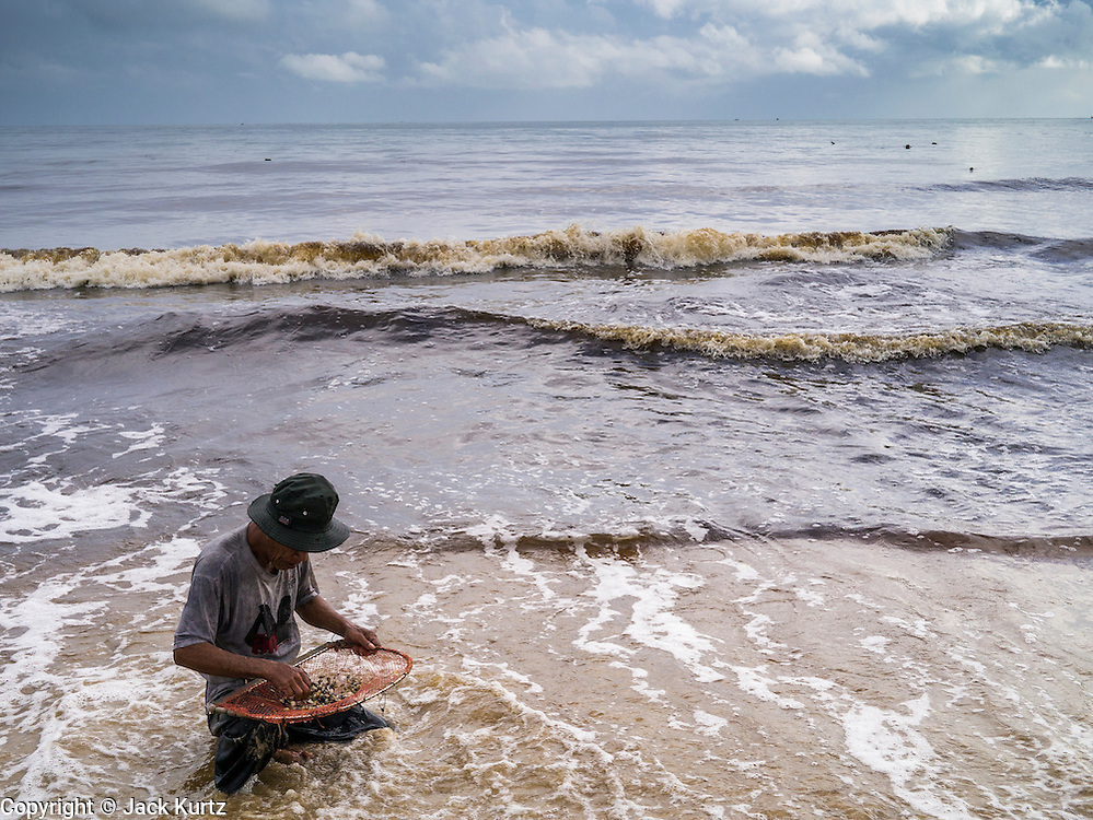 04 NOVEMBER 2012 - KAO SENG, SONGKHLA, THAILAND:  A man looks for snails and clams in the surf in Kao Seng. Kao Seng is a traditional Muslim fishing village on the Gulf of Siam near the town of Songkhla, in the province of Songkhla. In general, their boats go about 4AM and come back in about 9AM. Sometimes the small boats are kept in port because of heavy seas or bad storms.    PHOTO BY JACK KURTZ