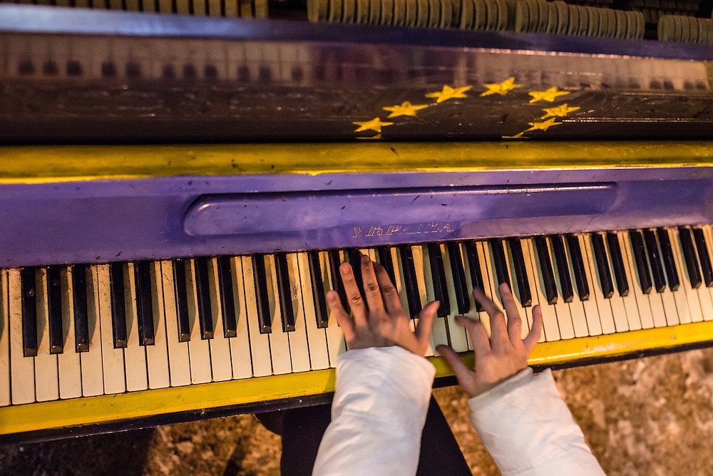 KIEV, UKRAINE - DECEMBER 11: A woman plays a piano with a European Union flag painted on it outside the Kiev City Hall, which is occupied by anti-government, pro-EU protesters, on December 11, 2013 in Kiev, Ukraine. Thousands of people have been protesting against the government since a decision by Ukrainian president Viktor Yanukovych to suspend a trade and partnership agreement with the European Union in favor of incentives from Russia. (Photo by Brendan Hoffman/Getty Images) *** Local Caption ***
