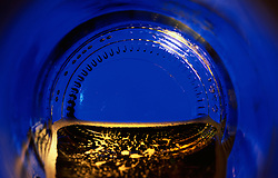 """Beauty at the Bottom: Blue""- This image is a photograph of a beer bottle shot right down the mouth of the bottle. A television provides the main light source."