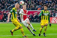 AMSTERDAM - Ajax - ADO , Voetbal , Eredivisie , Seizoen 2016/2017 , Amsterdam ArenA , 29-01-2017 ,  eindstand 3-0 , Ajax speler Donny van de Beek (m) tikt de bal over ADO Den Haag speler Tom Beugelsdijk (l) en ADO Den Haag speler Tyronne Ebuehi (r) heen