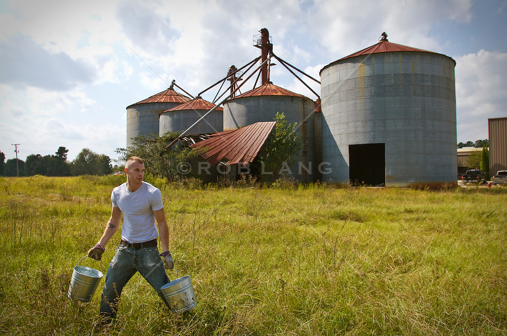 man walking with buckets while working on an industrial farm