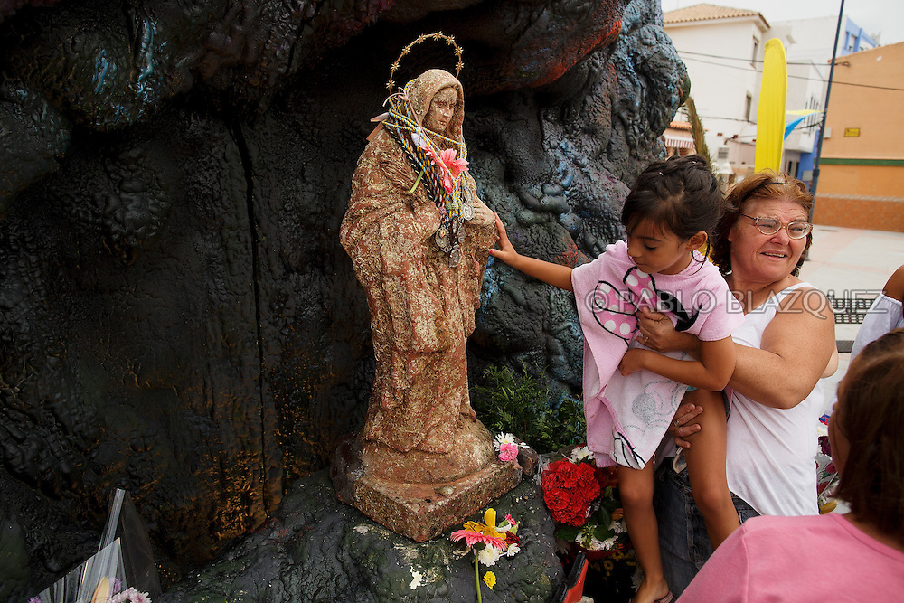 15/08/2016. Worshippers touch the Virgin of Palm image during the yearly Virgin of Palm maritime pilgrimage at El Rinconcillo beach on August 15, 2016 in Algeciras, Spain. The Our Lady of Palm maritime pilgrimage in Algeciras dates back to 1975 and takes place annually when fishermen rescue the submerged virgin from the deep sea. Worshippers amid thousands of visitors await its arrival at the Rinconcillo beach. The devotion for the Virgin of Palm comes from the seventeenth century when a ship coming from Italy docked at Algeciras port to wait out bad weather. According to legend, once the crew of the ship removed a box with an image of the Virgin from its cargo the weather turned and the sea's tides were calmed. (© Pablo Blazquez)