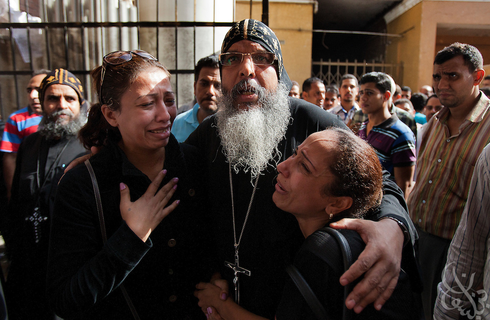 An Egyptian Coptic Christian cleric consoles relatives of the victims of sectarian violence October 10, 20011 at the Coptic Hospital in Cairo, Egypt. At least 26 people, mostly Christian, were killed during sectarian clashes that saw the worst violence since the Revolution that toppled former Egyptian president Hosni Mubarak earlier this year. Egyptian Coptic Christians make up about 10% of Egypt's 80 million population and periodically violence flares between the Christian minority and the majority Muslim population. (Photo by Scott Nelson)