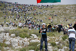 Palestinian refugees further up the mountain look on as others protest at the border fence in the valley below.