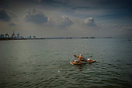 """Man on a """"kayak"""" made by recovered bamboo and styrofoam paddles out into Manila Bay to go fishing because he cannot afford a fishing boat.  Manila Bay, off of Baseco slum, Manila, Philippine."""